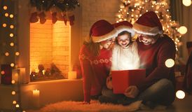 Merry Christmas! happy family mother father and child with magic. Gift near tree stock images