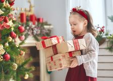Girl with Christmas presents. Merry Christmas and Happy Holiday! Cute little child girl with present gift boxes near tree at home royalty free stock image