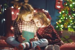 Girls with present. Merry Christmas and Happy Holiday! Cute little children girls with present gift box near tree at home Stock Photo