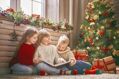 Children at Christmas. Merry Christmas and Happy Holiday! Cute little children reading the book near tree at home Stock Image