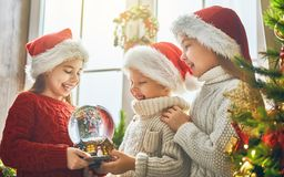 Children with snow globe. Merry Christmas and Happy Holiday! Cute little children with snow globe near tree at home royalty free stock photography
