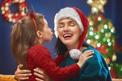 Mom and daughter near the Christmas tree Royalty Free Stock Image