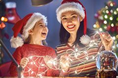 Mom and daughter near the Christmas tree Stock Photos