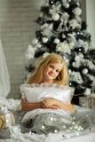 Merry Christmas and Happy Holiday. Pretty blonde girl is holding pillow near xmas tree Stock Photos