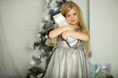 Merry Christmas and Happy Holiday. Pretty blonde girl is holding xmas gift Royalty Free Stock Photo