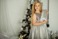 Merry Christmas and Happy Holiday. Pretty blonde girl is holding xmas gift Stock Photos