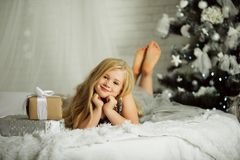 Merry Christmas and Happy Holiday. Pretty blonde girl is near decorated xmas tree Stock Photography