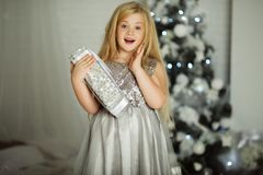 Merry Christmas and Happy Holiday. Pretty blonde girl with long hair is holding xmas gift Royalty Free Stock Image