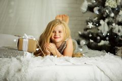 Merry Christmas and Happy Holiday. Pretty blonde girl is near decorated xmas tree Royalty Free Stock Photo