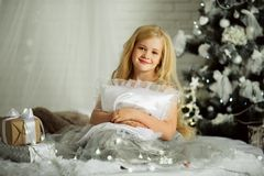 Merry Christmas and Happy Holiday. Pretty blonde girl is holding xmas gift Royalty Free Stock Image