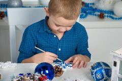 Merry Christmas and happy holidays!A boy painting a snowflake. Child creates decorations for Christmas interior. Merry Christmas royalty free stock photos