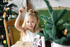 Merry Christmas and Happy Holidays. Cheerful cute child girl opening a Christmas present. Merry Christmas and Happy Holidays. Cheerful child girl opening a Royalty Free Stock Images