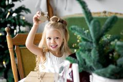Merry Christmas and Happy Holidays. Cheerful cute child girl opening a Christmas present. Merry Christmas and Happy Holidays. Cheerful child girl opening a Stock Photography