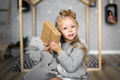 Merry Christmas and Happy Holidays. Cheerful cute child girl opening a Christmas present. Merry Christmas and Happy Holidays. Cheerful child girl opening a Royalty Free Stock Photos