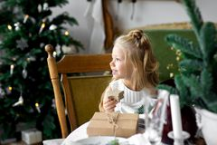 Merry Christmas and Happy Holidays. Cheerful cute child girl opening a Christmas present. Merry Christmas and Happy Holidays. Cheerful child girl opening a Stock Images