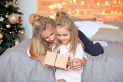 Merry Christmas and Happy Holidays.Cheerful cute children opening gifts. Kids having fun near tree in the morning stock photography