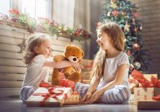 Girls opening gifts. Merry Christmas and Happy Holidays! Cheerful cute childrens girls opening gifts. Kids wearing pajamas having fun near tree in the morning Royalty Free Stock Images