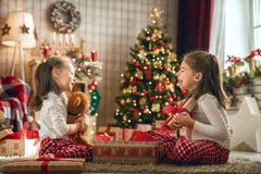 Girls opening Christmas gifts stock photo
