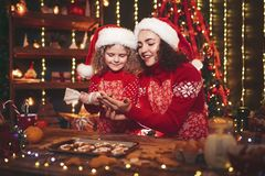 Merry Christmas and Happy Holidays. Cheerful cute curly little girl and her older sister in santas hats cooking royalty free stock images