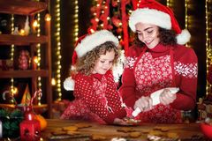 Merry Christmas and Happy Holidays. Cheerful cute curly little girl and her older sister in santas hats cooking stock images