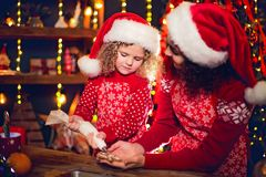 Merry Christmas and Happy Holidays. Cheerful cute curly little girl and her older sister in santas hats cooking royalty free stock photos