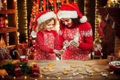 Merry Christmas and Happy Holidays. Cheerful cute curly little girl and her older sister in santas hats cooking. Merry Christmas and Happy Holidays. Family stock images