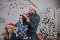 Merry Christmas and Happy Holidays Cheerful mom, dad and her cute daughter dress each other`s Christmas hats. Parent and. Little child having fun near Christmas Royalty Free Stock Photos
