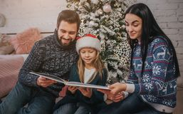 Merry Christmas and Happy Holidays Cheerful mom, dad and her cute daughter girl reading a book. Parent and little child. Merry Christmas and Happy Holidays Stock Photo