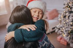 Merry Christmas and Happy Holidays Cheerful mom and her cute daughter girl exchanging gifts. Parent and little child. Having fun near Christmas tree indoors Royalty Free Stock Images