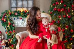 Merry Christmas and Happy Holidays Cheerful mom and her cute daughter girl exchanging gifts. Parent and little child having fun royalty free stock image