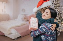 Merry Christmas and Happy Holidays Cheerful mom and her cute daughter girl exchanging gifts. Parent and little child. Having fun near Christmas tree indoors Royalty Free Stock Image