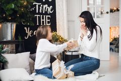 Merry Christmas and Happy Holidays. Cheerful mom and her cute daughter girl opening a Christmas present. Parent and royalty free stock photo
