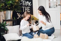 Merry Christmas and Happy Holidays! Cheerful mom and her cute daughter girl opening a Christmas present. Parent and. Little child having fun near Christmas tree Royalty Free Stock Photo