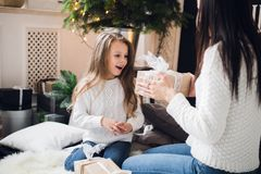 Merry Christmas and Happy Holidays. Cheerful mom and her cute daughter girl opening a Christmas present. Parent and. Little child having fun near Christmas tree Stock Photo