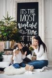 Merry Christmas and Happy Holidays. Cheerful mom and her cute daughter girl opening a Christmas present. Parent and. Little child having fun near Christmas tree Stock Photos