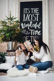 Merry Christmas and Happy Holidays. Cheerful mom and her cute daughter girl opening a Christmas present. Parent and. Little child having fun near Christmas tree Royalty Free Stock Photo