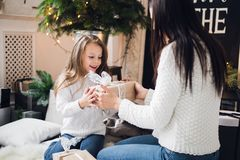 Merry Christmas and Happy Holidays. Cheerful mom and her cute daughter girl opening a Christmas present. Parent and. Little child having fun near Christmas tree Stock Image