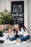 Merry Christmas and Happy Holidays. Cheerful mom and her cute daughter girl opening a Christmas present. Parent and. Little child having fun near Christmas tree Royalty Free Stock Photography