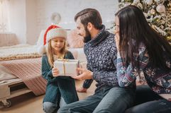 Merry Christmas and Happy Holidays Cheerful Mother, father and her cute daughter girl exchanging gifts. Parent and. Little child having fun near Christmas tree Stock Image