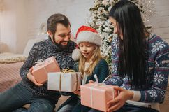 Merry Christmas and Happy Holidays Cheerful Mother, father and her cute daughter girl exchanging gifts. Parent and. Little child having fun near Christmas tree Stock Photos