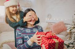 Merry Christmas and Happy Holidays Cheerful Mother, father and her cute daughter girl exchanging gifts. Parent and. Little child having fun near Christmas tree Royalty Free Stock Photography