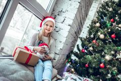 Merry Christmas and happy holidays! Cute little baby girl sitting by the window royalty free stock photos