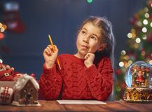 Girl is writing the letter to Santa Royalty Free Stock Photos