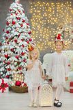 Merry Christmas and Happy Holidays Cute little child girls decorating the white green Christmas tree indoors with alot of presents Stock Image