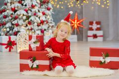 Merry Christmas and Happy Holidays Cute little child girls decorating the white green Christmas tree indoors with alot of presents Stock Photo