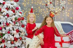 Merry Christmas and Happy Holidays Cute little child girls decorating the white green Christmas tree indoors with alot of presents Royalty Free Stock Images