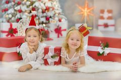 Merry Christmas and Happy Holidays Cute little child girls decorating the white green Christmas tree indoors with alot of presents Stock Photos