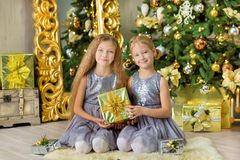 Merry Christmas and Happy Holidays Cute little child girls decorating the white green Christmas tree indoors with alot of presents Royalty Free Stock Image