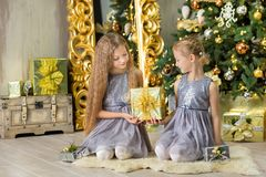 Merry Christmas and Happy Holidays Cute little child girls decorating the white green Christmas tree indoors with alot of presents Stock Images
