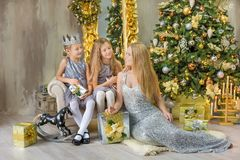 Merry Christmas and Happy Holidays Cute little child girls decorating the white green Christmas tree indoors with alot of presents Royalty Free Stock Photography